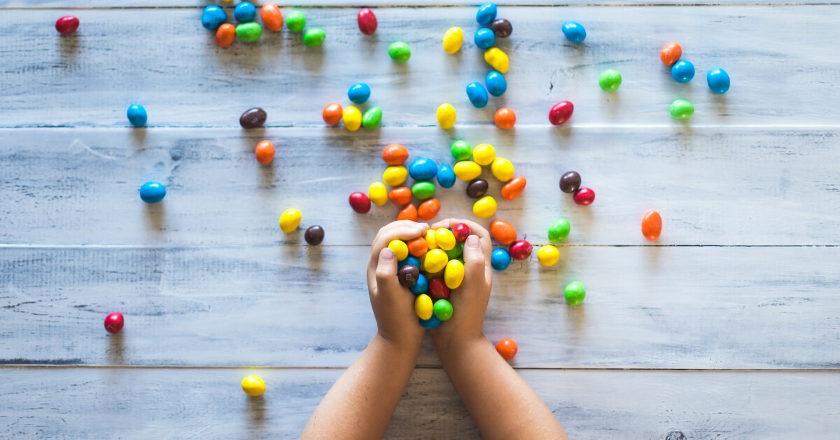 kid holding coloured candy