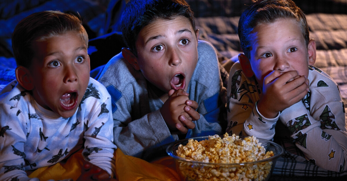 scared kids watching a movie with bowl of popcorn