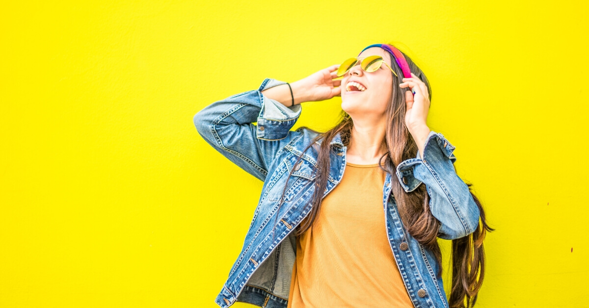 happy woman wearing sunglasses in front of a yellow wall
