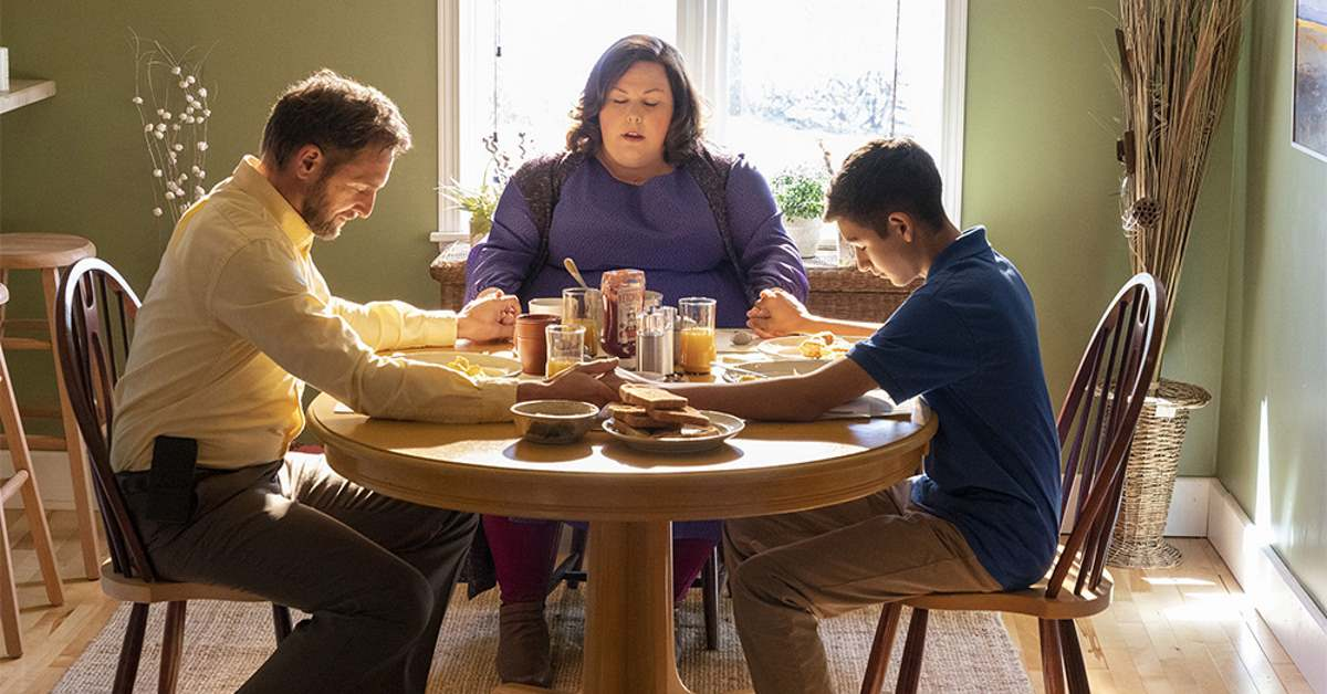 Scene from the movie Breakthrough with Father, Mother and Son holding hand in prayer around a table before a meal