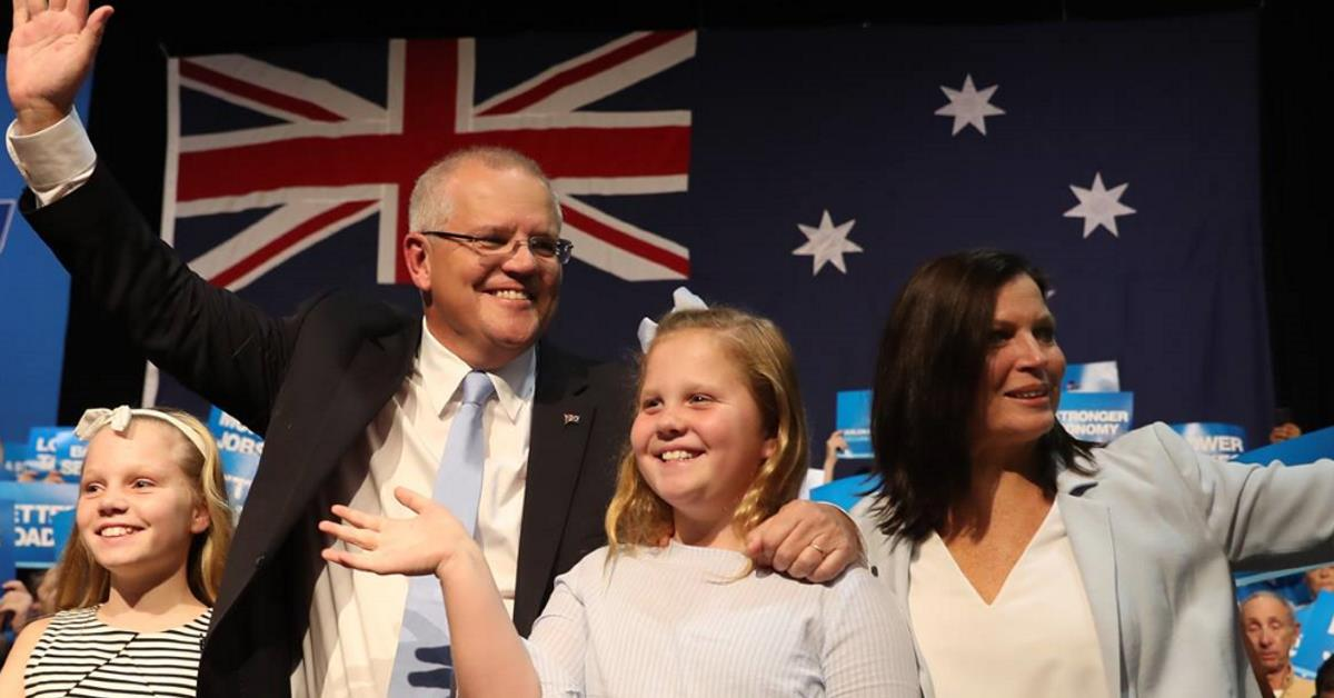 Scott Morrison and his family waving to supporters in front of an Australian flag