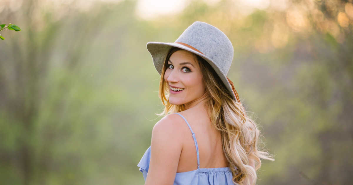 Woman in grey felt hat looking over her shoulder smiling