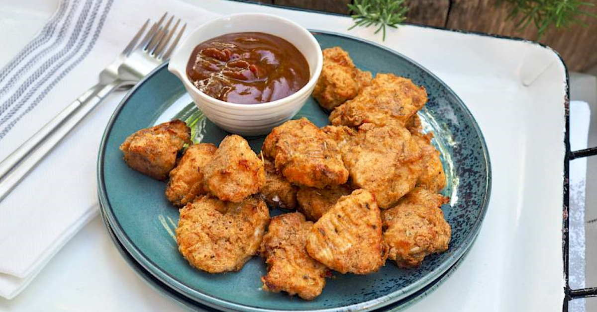 a plate full of chicken nuggets with a bowl of dipping sauce