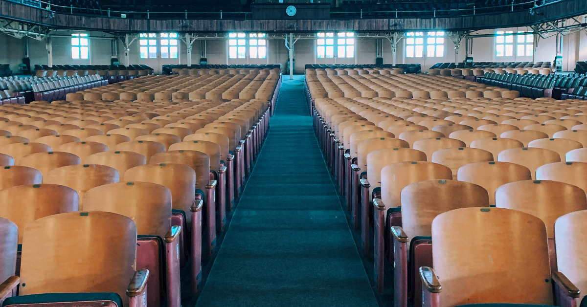 Rows of empty chairs in a large auditorium church like building
