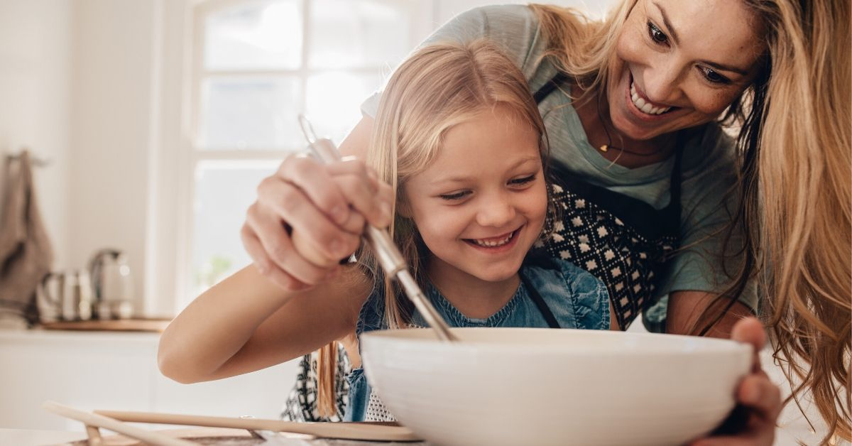 photo of a happy mum and daughter stirring a baking bowl to make chocolate eggs for easter