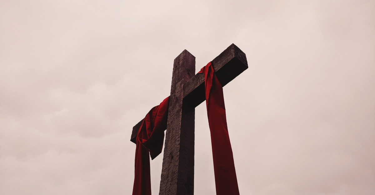 looking up at wooden cross towards sky red sash draped over cross
