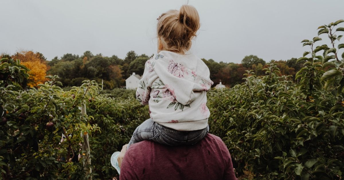 photo of a young girl sitting on her dad's shoulders