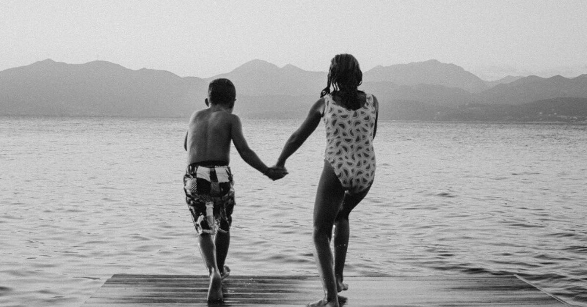 black and white photo of two kids in bathing suits holding hands jumping off a pier into the water