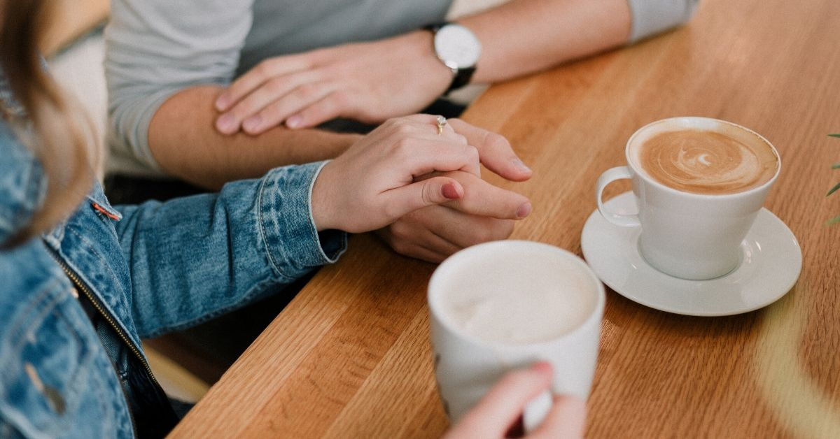 photo of a woman and man sitting at a table drinking coffee with the woman's hand on top of his