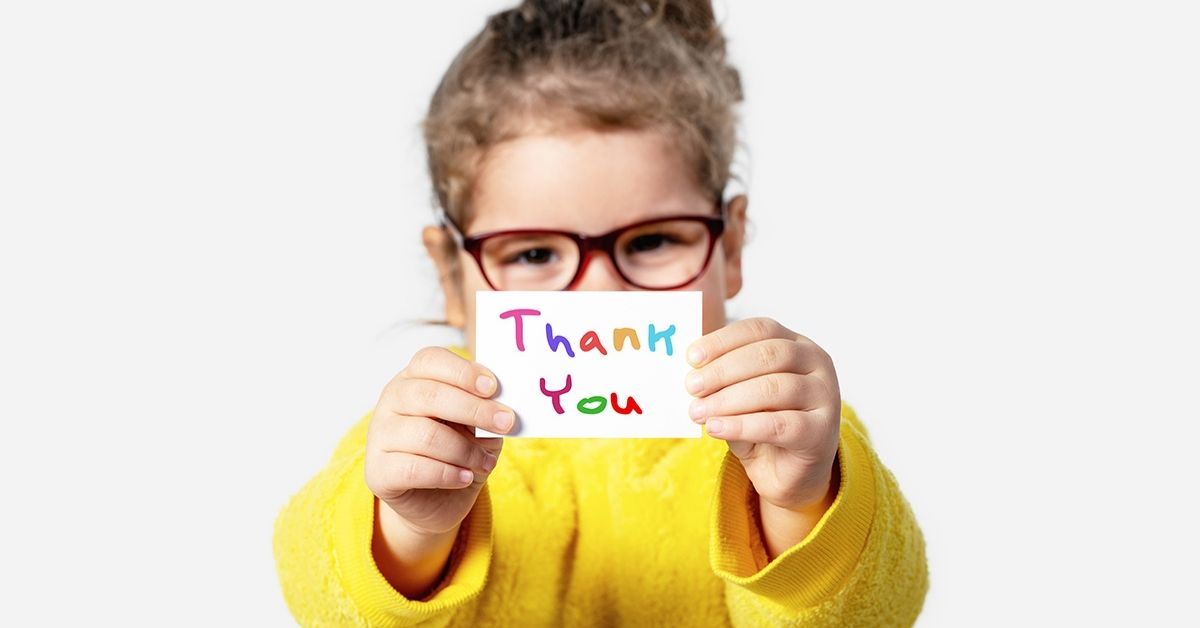 "photo of a young girl holding a paper in front of her which says thank ""thank you"" in colourful letters."