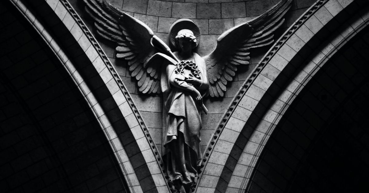 photo shows a shadowy stone angel statue