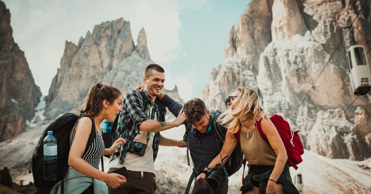 photo of a group of friends hikinh with mountains in the background, laughing