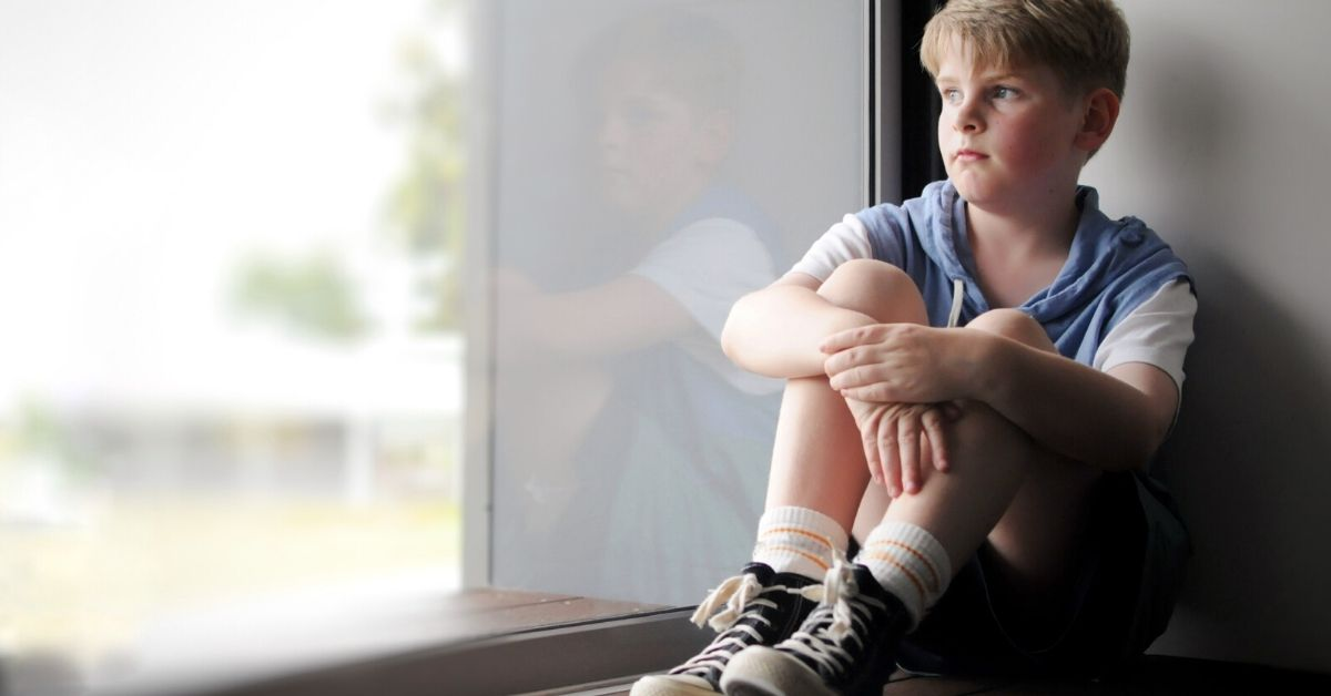 photo of a school aged child looking out the window