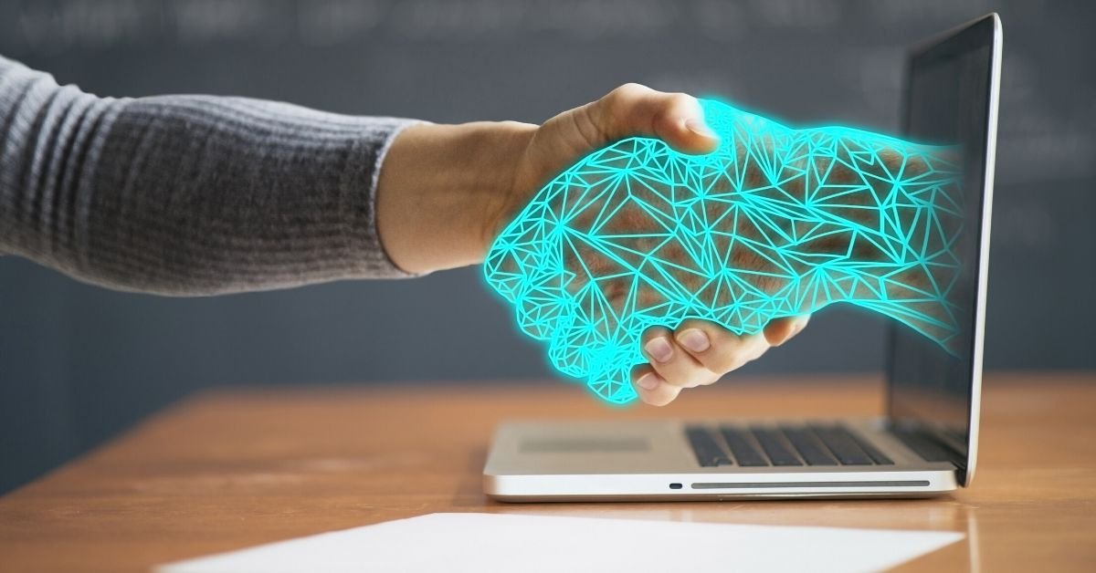 photo of a digital illustrated arm coming out of a computer screen, shaking the hand of a human