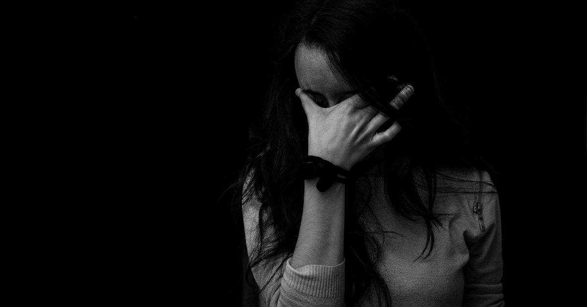 black and white photo of a distraught woman with her face in her hand