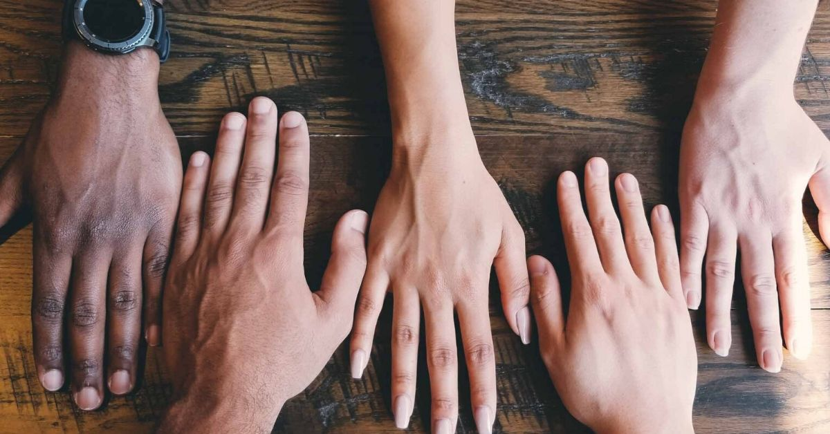 photo representing the concept of migration which depicts different coloured skin toned hands side by side on a wooden table