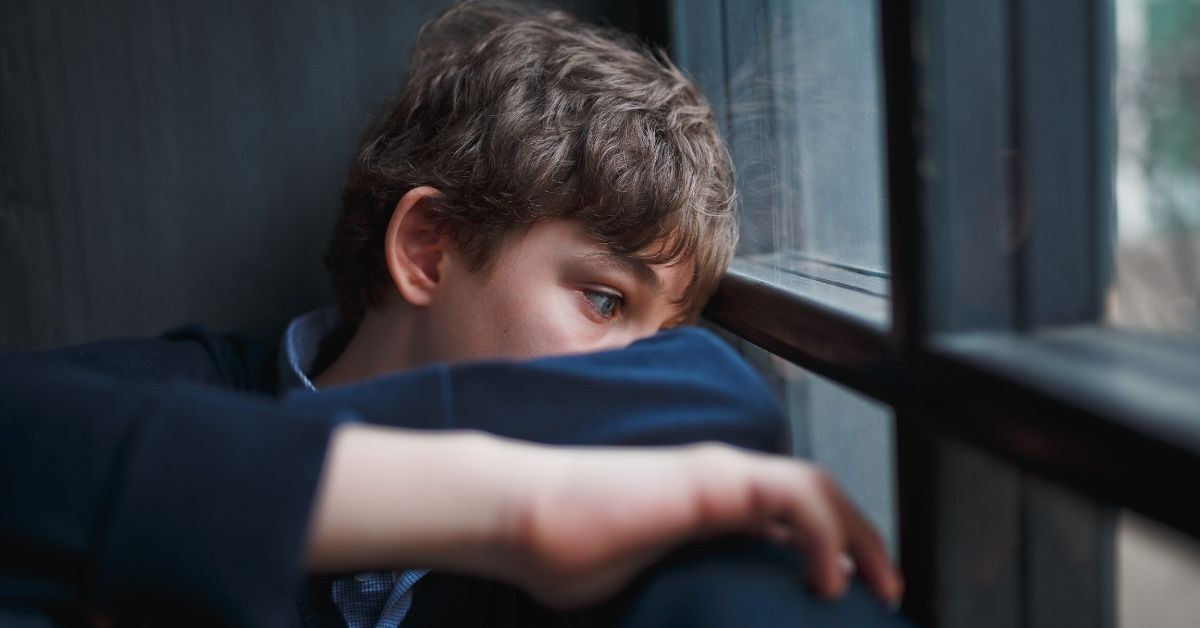 boy sitting gazing out the window with arms around knees
