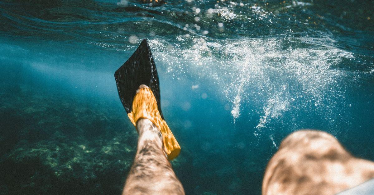 man's flippers underwater stirring the water