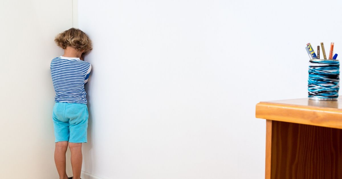 photo of a child standing in the corner with face in hands