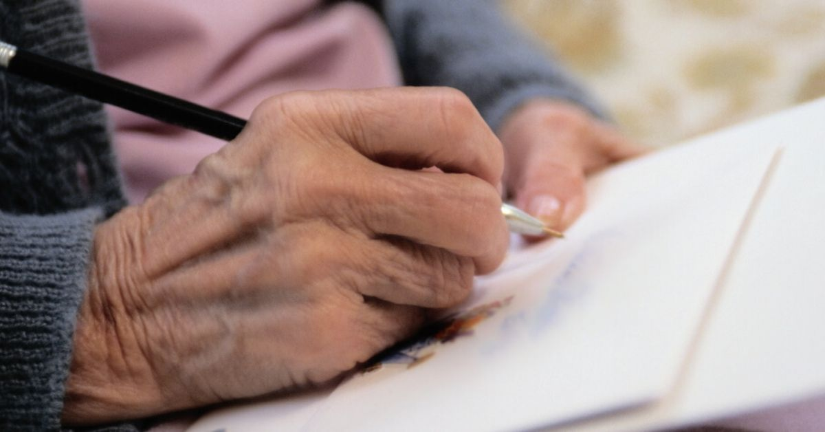 photo depicts close up photo of a hand writing a letter