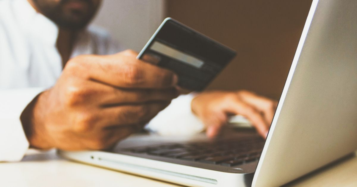 close up photo of a man's hand holding a credit card as he types on his computer