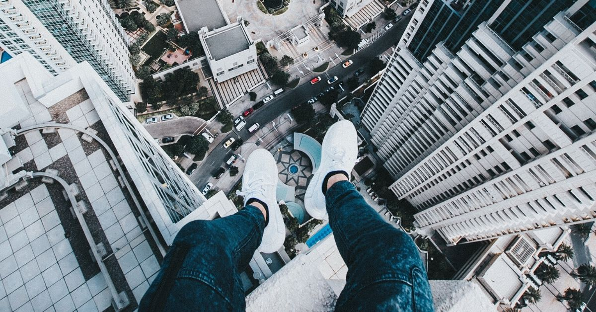 man's feet hanging off the edge of a tall building