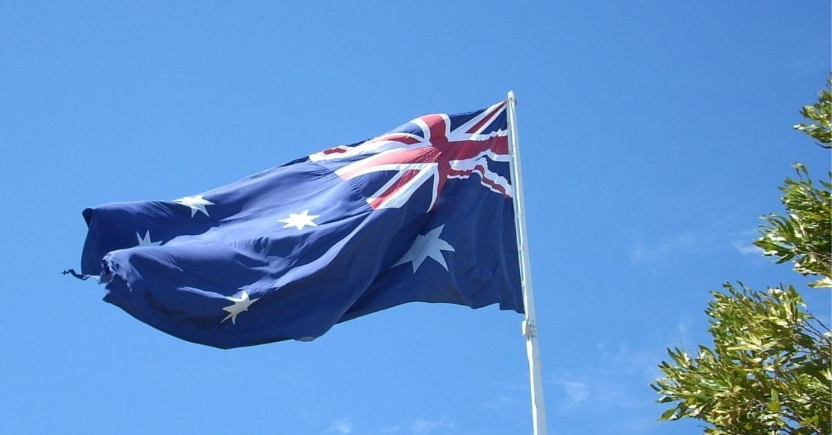 an australian flag flying slightly fraying on the ends