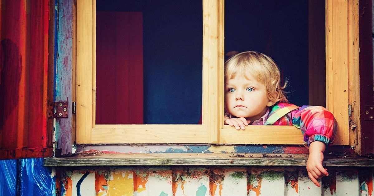 child gazing blankly out of a window