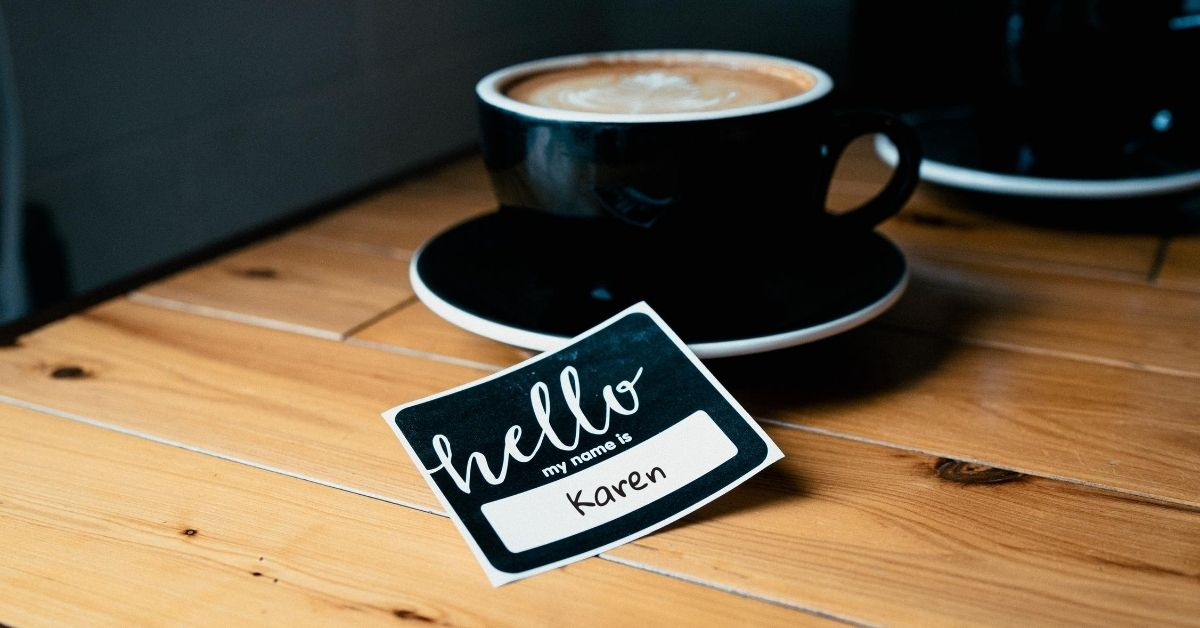 name tag next to mug of coffee which reads hello my name is karen