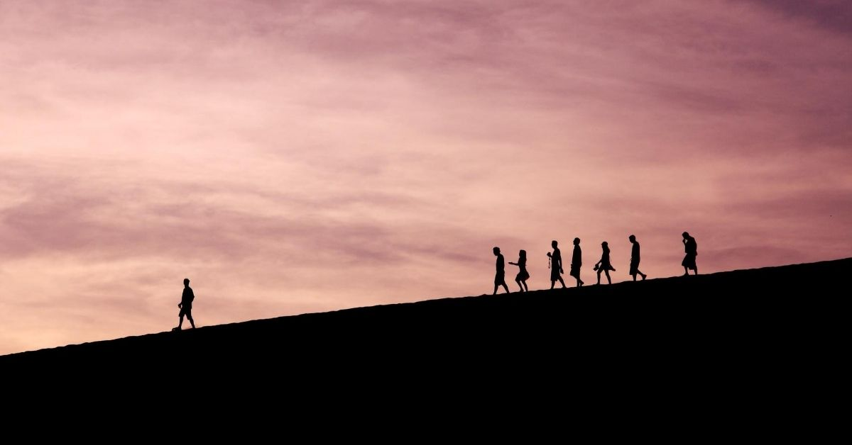silhouette of a leader walking in front of a group down a mountain