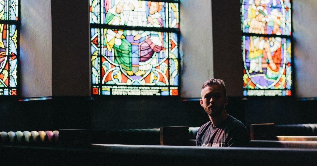 man sitting in a church pew alone