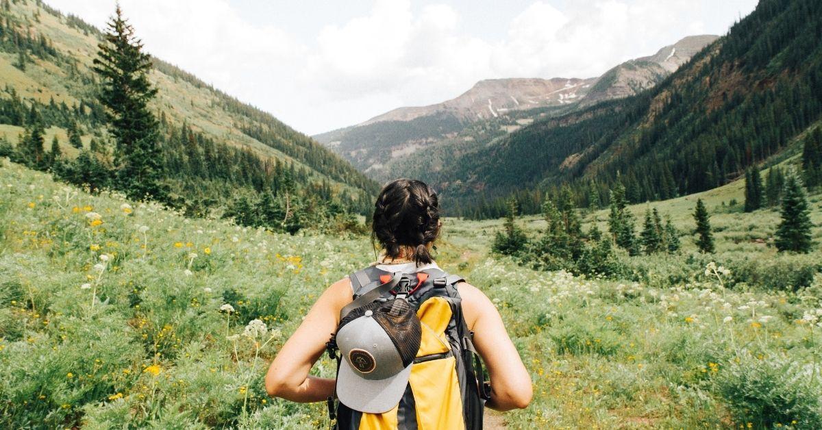 man hiking through a valley