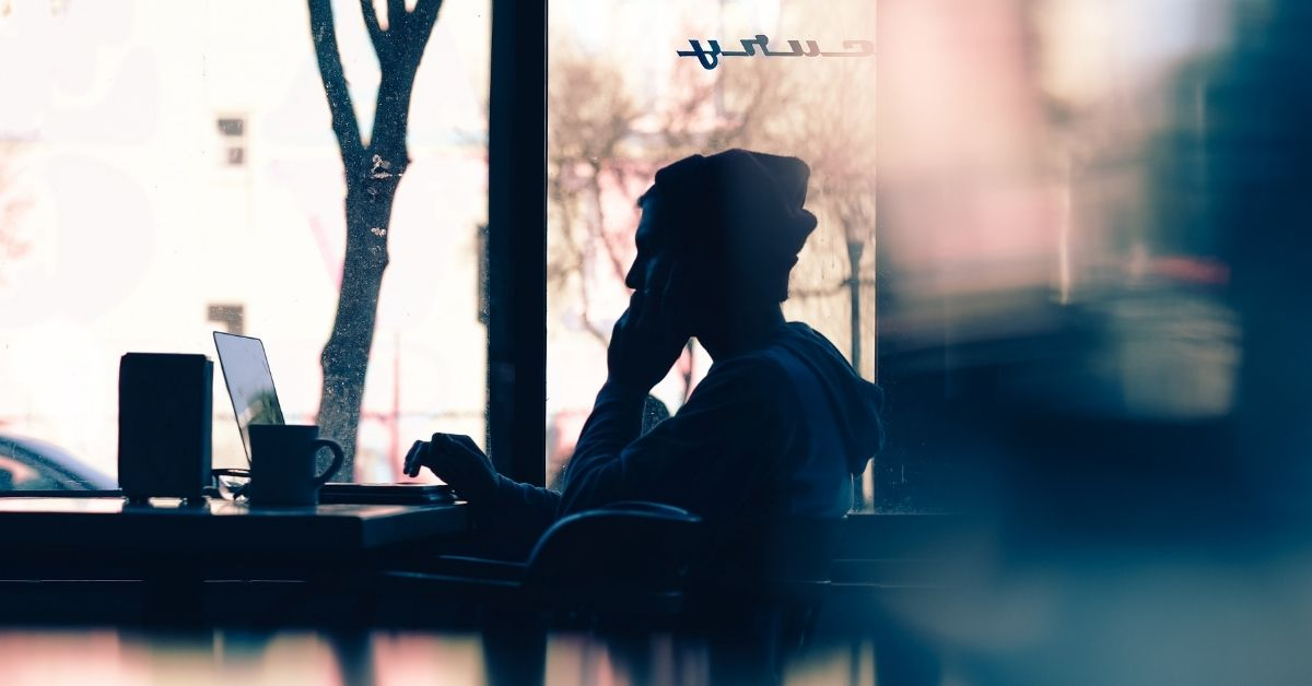 a silhouette of a man talking on the phone in a coffee shop